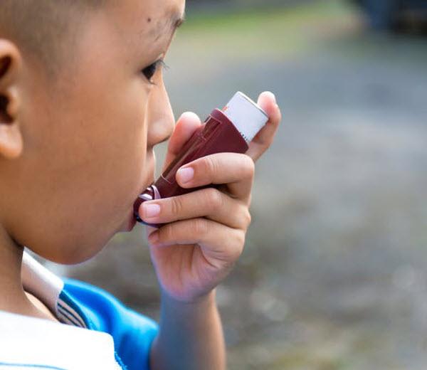 DG - a boy using an inhaler