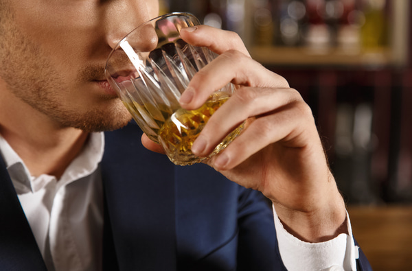 Closeup of a man drinking whiskey