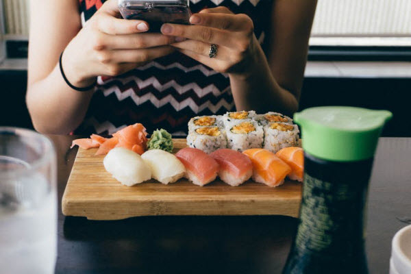 Woman using a mobile phone with sushi on her table