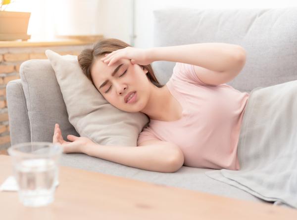 DG - Young beautiful woman on sofa having headache,stress and sick