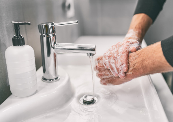 Man rubbing his hands with soap