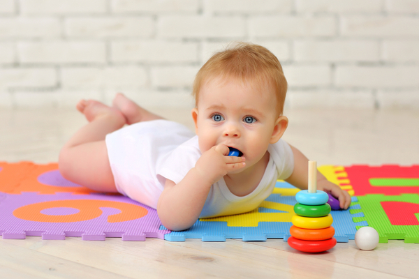 An infant putting a toy inside her mouth