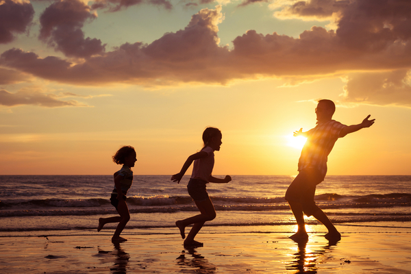 Father with kids having fun on the shore