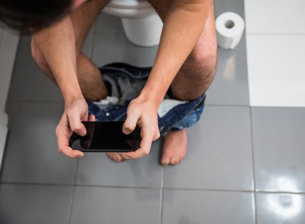 Man in toilet using phone