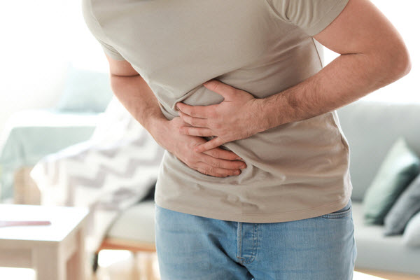 Man suffering from stomachache at home