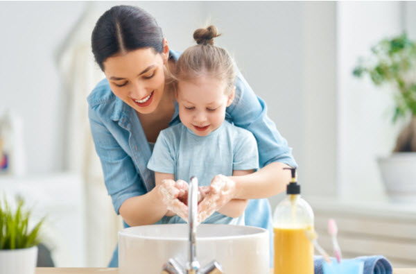 Mother and daughter happily washing hands